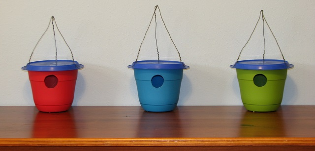 Here are three completed flower pot birdhouses--one red, one blue, and one green.